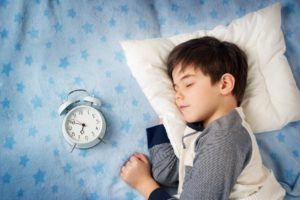 child sleeping with a clock